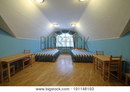 Empty room with two beds near a large window and wooden furniture