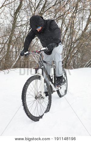 Young man riding a bicycle on snow in winter