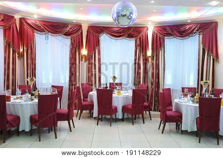 Beautiful banquet hall with round served tables, red chairs and drapes and color music on the ceiling
