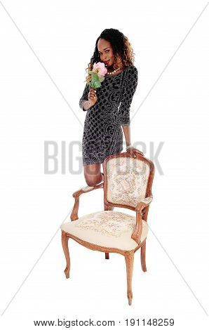 A pretty African American woman in a short dress standing behind an old fashioned armchair smelling the rose isolated for white background.