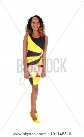 A beautiful African American slim woman standing in a black and yellow dress holding her purse isolated for white background.