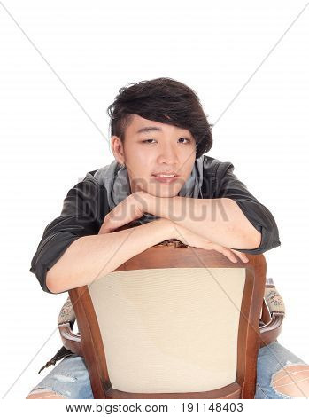 A young good looking Asian teenager sitting backwards on an old armchair with his arms crossed isolated for white background.