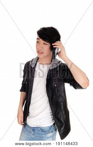 An Asian teenager talking at his cell phone and is worried what he hears from his phone isolated for white background.