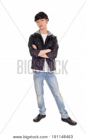 A serious Asian teenager standing in an black jacket crossing his arms standing isolated for white background.
