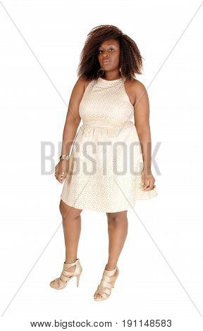 a portrait picture of a african american women in a beige dress and messy hair standing isolated for white background.