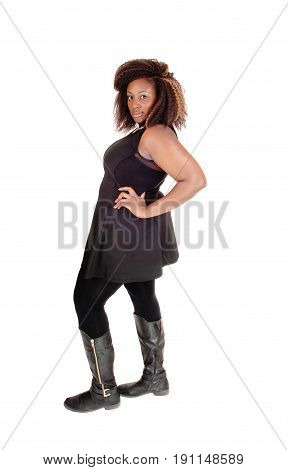 a full body picture on an african american woman in boots and a black dress standing isolated for white background in profile.