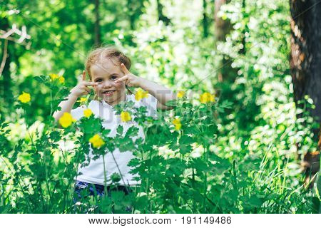 Adorable Little four Year Old Girl And Looking At Camera With Smile In Forest On Summer Day. Children Gathered Mushrooms.