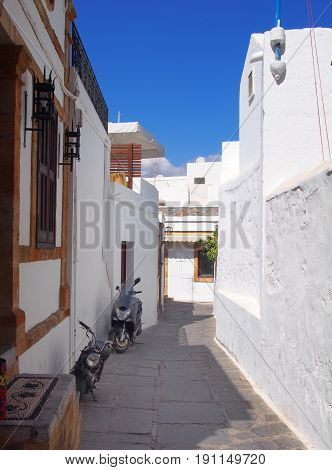 whitewashed village street in afandou in rhodes with blue shy doors and motorcycles