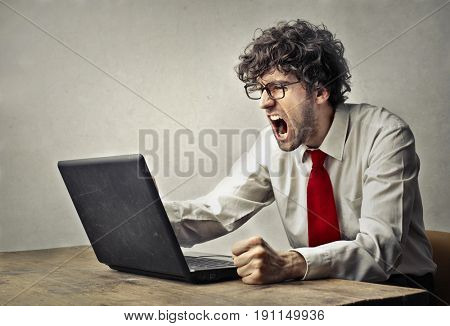 Frustrated employee shouting towards his laptop