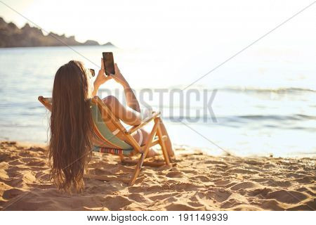 Long haired girl sitting in a beach chair sending a text message