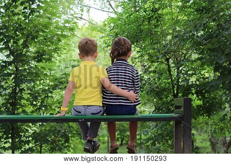 Photo from the back. Portraits of Caucasian cute boy and girl friends sitting together in park outside on summer day . boy hugging girl