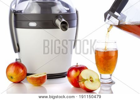Juicer and apple juice preparing healthy fresh juice on white background. Pouring juice in glass.