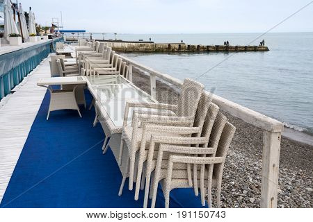 Row of wicker chairs stacked on each other and cafe tables along the embankment. Start/end of tourist season