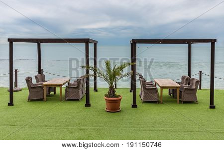 Wooden tables and wicker chairs overlooking sea and heaven. Palm tree in flowerpot
