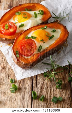 Tasty Baked Sweet Potato Stuffed With Fried Egg And Tomato Close-up. Vertical