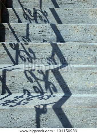 blue concrete or stone steps in sunlight with reflection of ornate railings