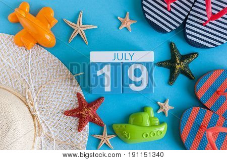 July 19th. Image of july 19 calendar with summer beach accessories and traveler outfit on background. Summer day, Vacation concept.