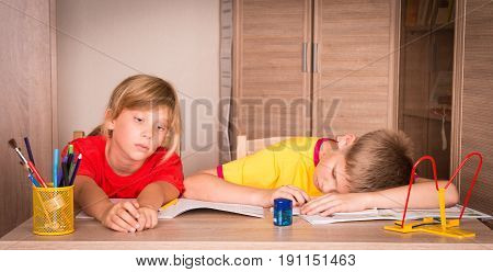Children with learning difficulties. Tired boy and bored girl doing homework. Education.