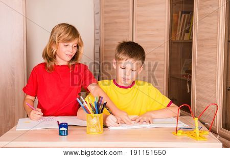 Sister helping her brother with home assignment. Portrait of two cute children working on their homework together. Boy and girl doing homework at home.