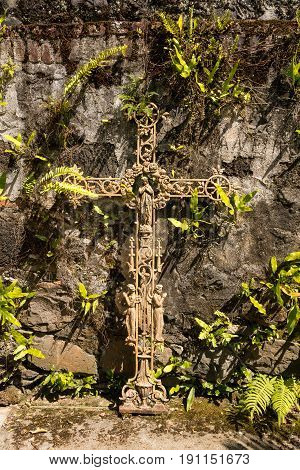 Ornate metal crucifix with statues of Mary and saints on old stone wall with plants growing into the shape