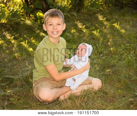 Portrait of happy brother and his newborn baby sister outdoor. Preteen boy with his little sister sitting on the grass summer day.