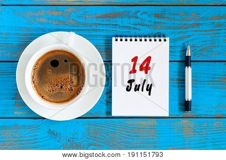 July 14th. Day 14 of month, calendar on blue wooden table background with morning coffee cup. Summer concept.