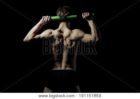 Athletic man athlete or bodybuilder with fit naked back torso shoulders holding baseball bat in strong arms on black background. Sport and training