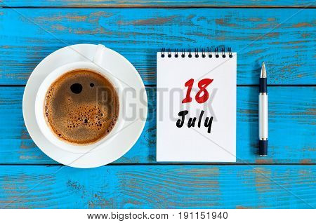 July 18th. Day 18 of month, calendar on blue wooden table background with morning coffee cup. Summer concept.