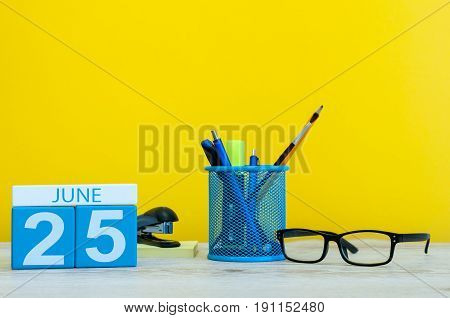June 25th. Day 25 of month, calendar on yellow background with office supplies. Summer time at work.