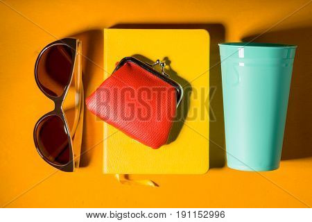 Sunglasses , purse , notebook and cup on the yellow background horizontal