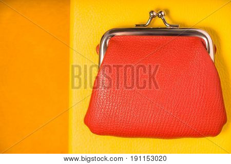 Orange purse on the bright yellow background top view horizontal