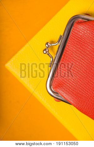 Orange purse on the bright yellow background top view vertical