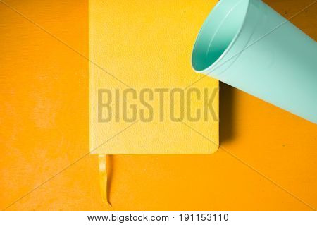 Blue plastic cup with notebook on the yellow background top view horizontal