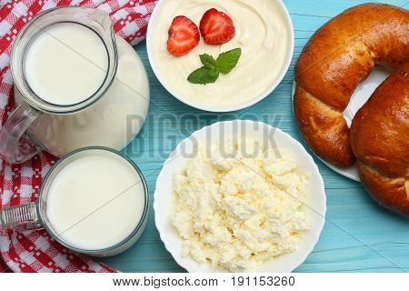 Milk background. Glass jug pitcher of fresh milk with glass, sour cream, cottage cheese and croissant on blue wooden background. Top view with copy space.