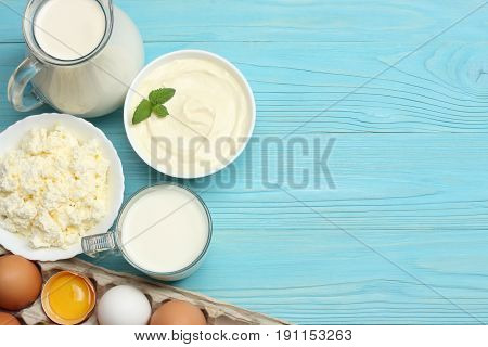 Milk background. Glass jug pitcher of fresh milk with glass, sour cream, cottage cheese and eggs on blue wooden background. Top view with copy space.