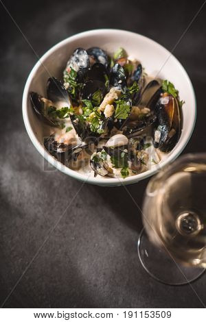 Mussels in Roquefort sauce  on the black stone background