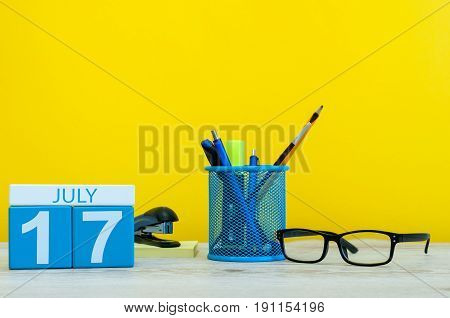 July 17th. Image of july 17, calendar on yellow background with office supplies. Summer time. With empty space for text.