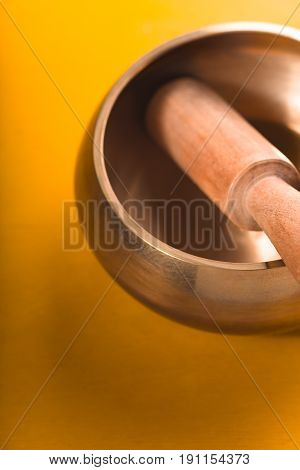 Tibetan singing bowl on the yellow background vertical
