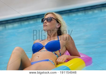 Blonde model posing in a water in an outdoor environment