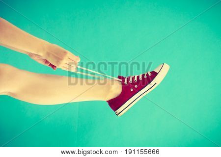 Footwear fashion shoes concept. Person tying laces in red sneaker with foot up studio shot on blue green background