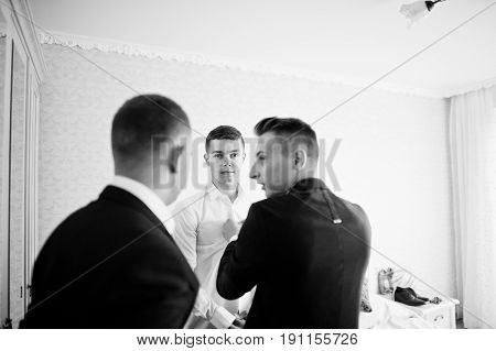 Groomsmen Helping Groom To Dress Up And Get Ready For His Wedding In A Room. Black And White Photo.