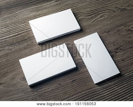 Three stacks of blank business cards on wood background. Template for your design. Template for ID. Responsive design mockup.