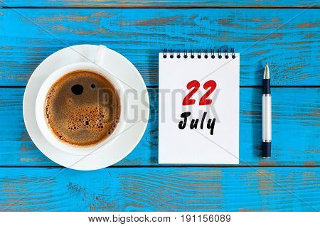 July 22nd. Day 22 of month, calendar on blue wooden table background with morning coffee cup. Summer concept.