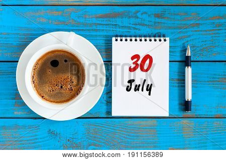 July 30th. Day 30 of month, calendar on blue wooden table background with morning coffee cup. Summer concept.