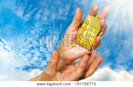 The bright picture of woman holding wooden house on blue sky. Concept of dream