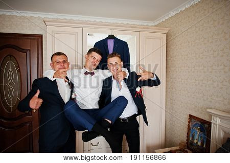 Handsome Groom And Groomsman In The Room Hugging Next To The Mirror.