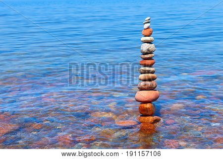 high pyramid of colored wet stones standing in water. Concept of balance and harmony