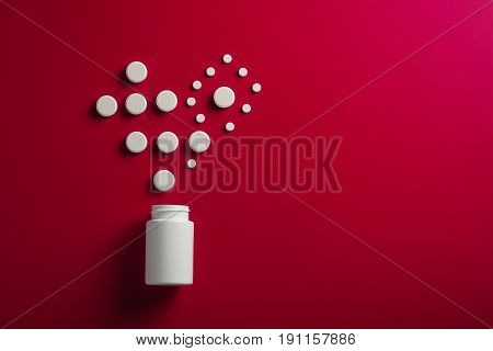 Medical Pills Heart Shape And Bright Bottle Red Background
