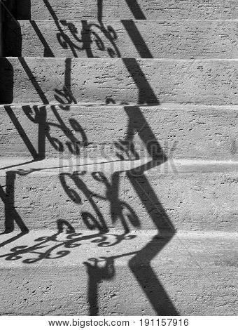 grey concrete steps with shadows of an ornate railing