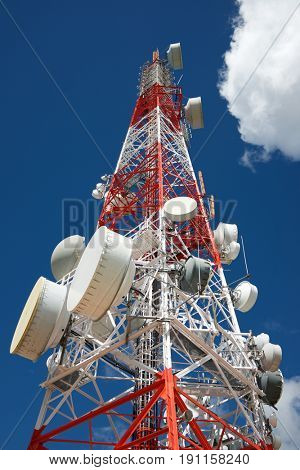Telecommunications tower with cloudy sky.